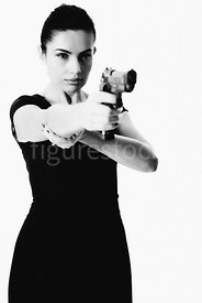 A woman standing pointing a gun – shot from mid level.