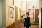 A woman takes a picture of a priapic satyr in the Secret Museum in Naples