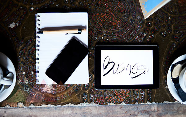 Still life with cell phone, tablet, pen and notebook on an antique table