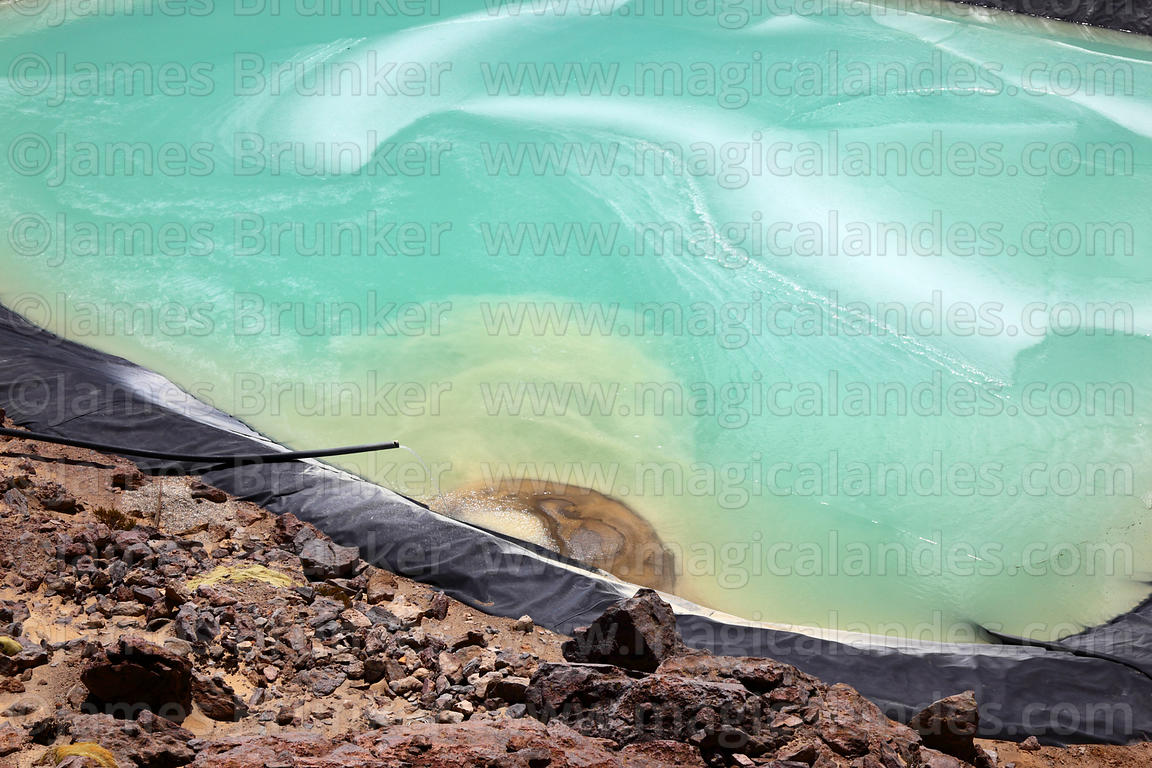 Detail of turquoise water, ice and sediment in settling basin, Acotango volcano, Oruro Department, Bolivia