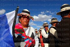 Woman wearing traditional dress holding MAS party flag at festival, Orinoca, Bolivia