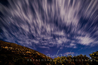 Star and cloud trails in night sky above mountan