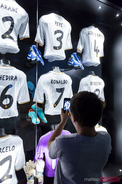 Boy taking photo of Real Madrid football shirts, Spain