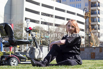 Woman sitting on the grass at a city park with her mobility scooter