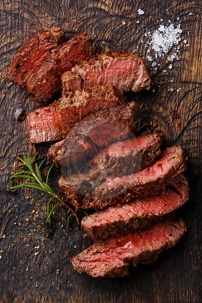 Sliced medium rare grilled Beef steak on wooden cutting board background