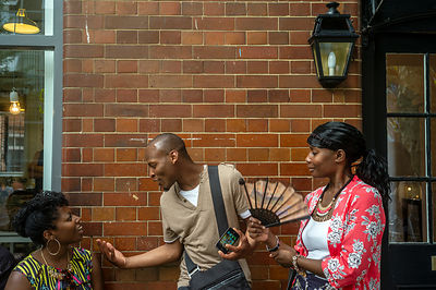 A man and two women converse on the street at the African street style Festival