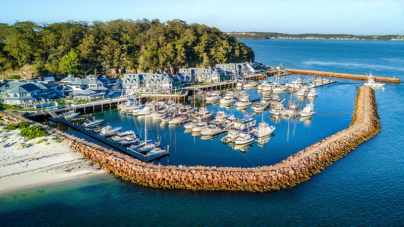 Views over boats and yachts moored at The Anchorage Marina Port Stephens.  Attached buildings offers a cafe restaurant  dinin...