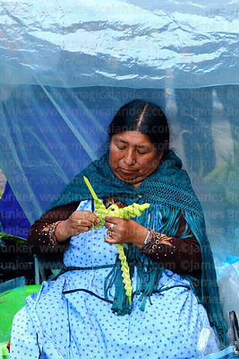 Woman making cross out of palm leaves on Palm Sunday, La Paz, Bolivia