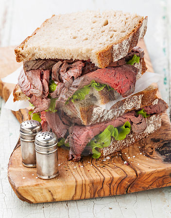 Roast beef sandwiches with lettuce on olive wood cutting board