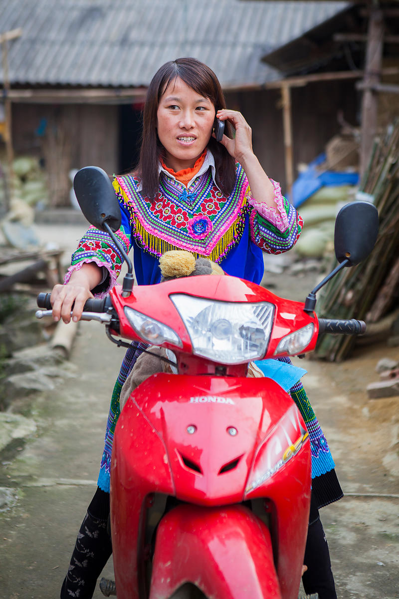 Femme en habit traditionnel téléphonant sur sa moto, Bac Ha, Vietnam / Women in traditional dress phoning on his motorcycle, ...