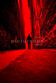 An atmospheric image of a mystery man walking down a narrow dark alley.