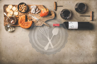 Wine bottle, glasses with wine and appetizers on wooden board