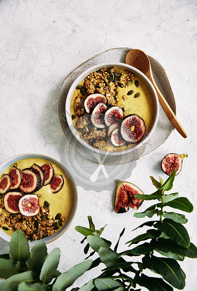 Healthy banana, trumeric, almond milk and oat breakfast bowl with fresh figs.