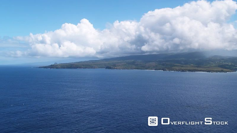 Approaching Maui under mounded white clouds.