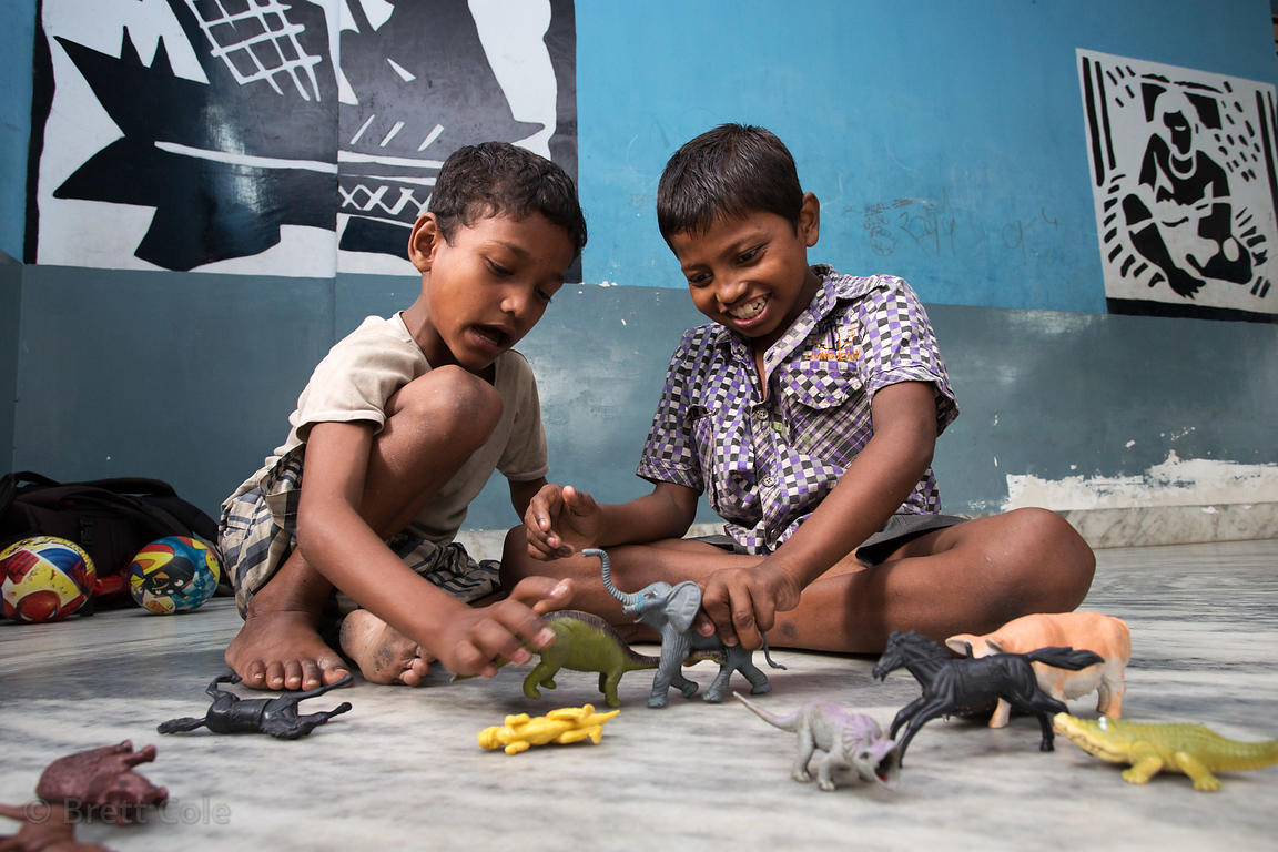 Children play with toy dinosaurs at a shelter in Calcutta, India