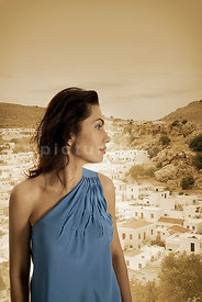An atmospheric image of a woman in a blue dress looking away over a greek village.