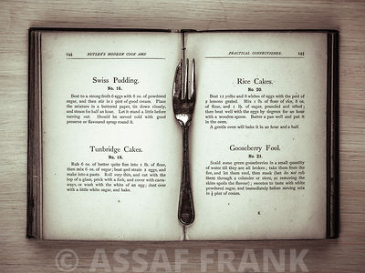 Old cookery book open with an old fork spoon
