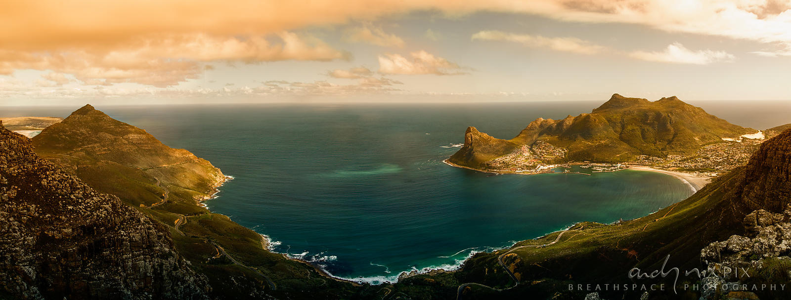 Panoramic view at sunset of Hout Bay, pink clouds reflecting in aqua sea, road along Chapman's Peak on left and town below th...