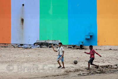 Two boys kick a soccer ball in front of a colorful wall at Juhu Beach, Mumbai, India.