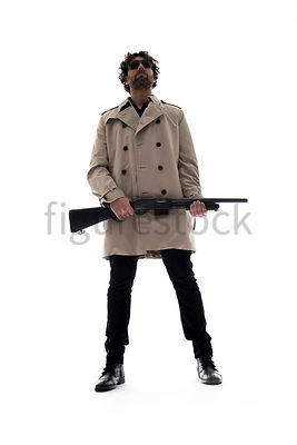 A Figurestock image of a man in a mac, standing, holding a shotgun – shot from low level.