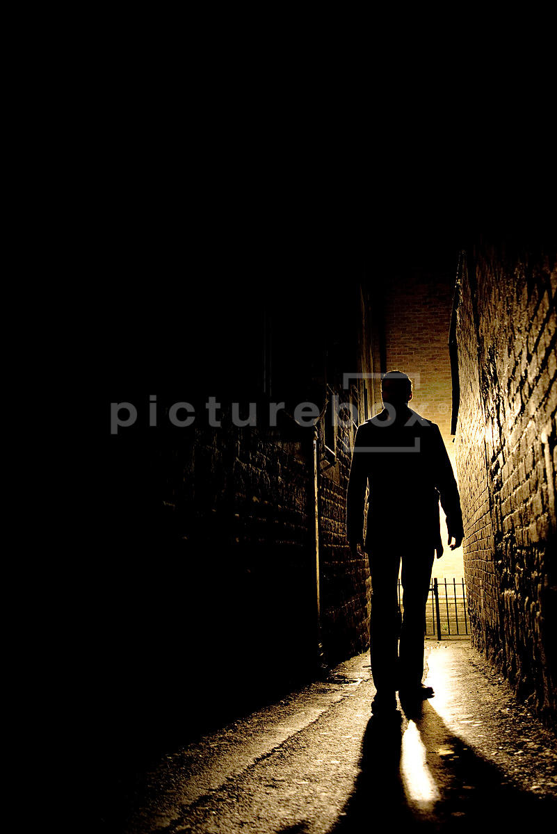 An atmospheric image of the silhouette of a mystery man, walking down an alley at night.