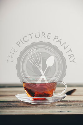 A cup of tea on the wooden table against the white wall