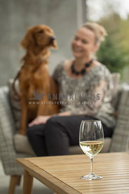 Blonde woman laughing with Irish Setter mix sitting on outdoor chair with white wine glass on table
