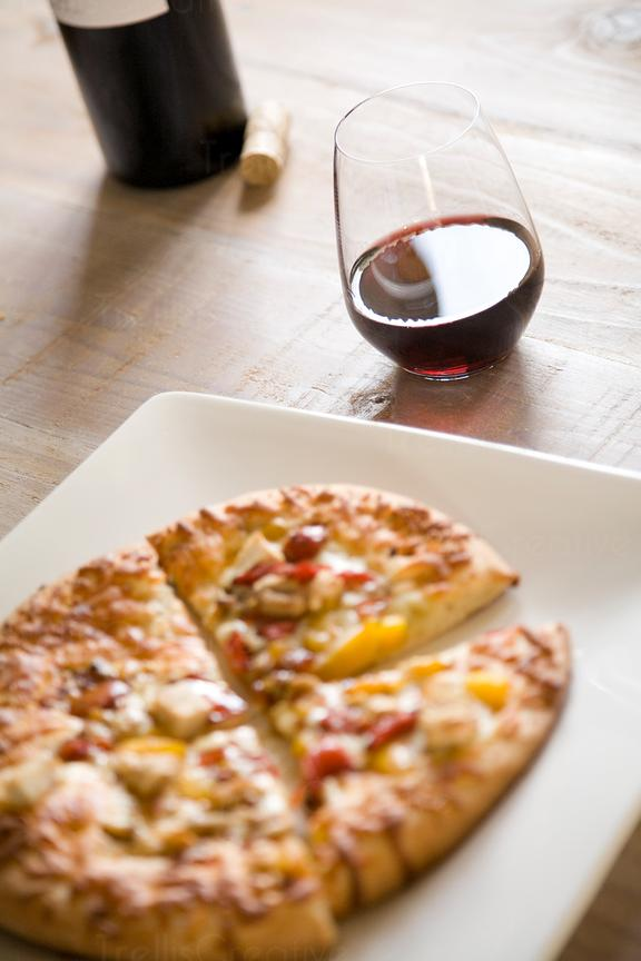 Stemless glass of red wine paired with pizza