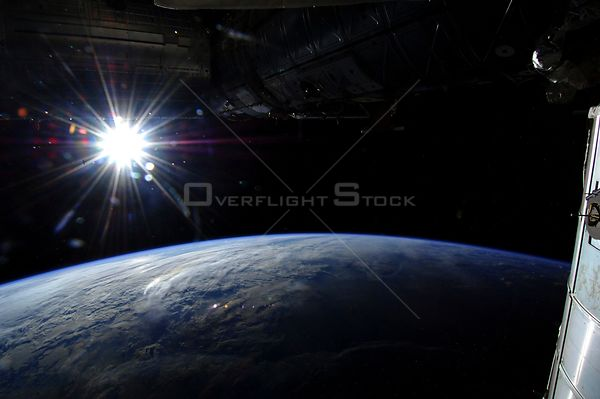 "ABOARD THE INTERNATIONAL SPACE STATION -- 21 May 2013 -- The sun is captured in a ""starburst"" mode over Earth's horizon by on..."