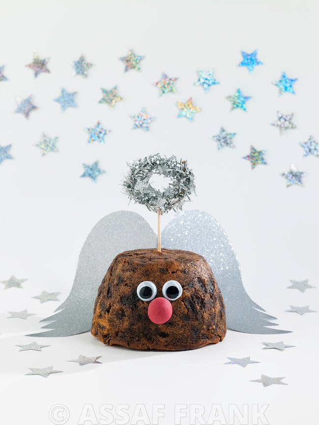 Christmas pudding decorated as an angel on white background