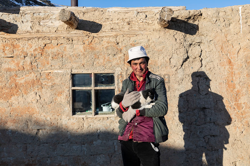Nurbol Holding a Cat in Front of his House
