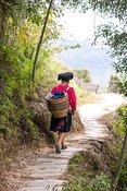 Yao ethnic minority woman walking on track carrying a load