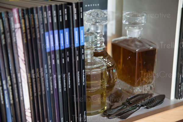 Close-up of books and whiskey decanters on a shelf