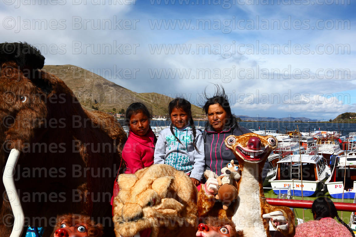 A local family have their photo taken with Ice Age film characters on Lake Titicaca waterfront, Puno, Peru