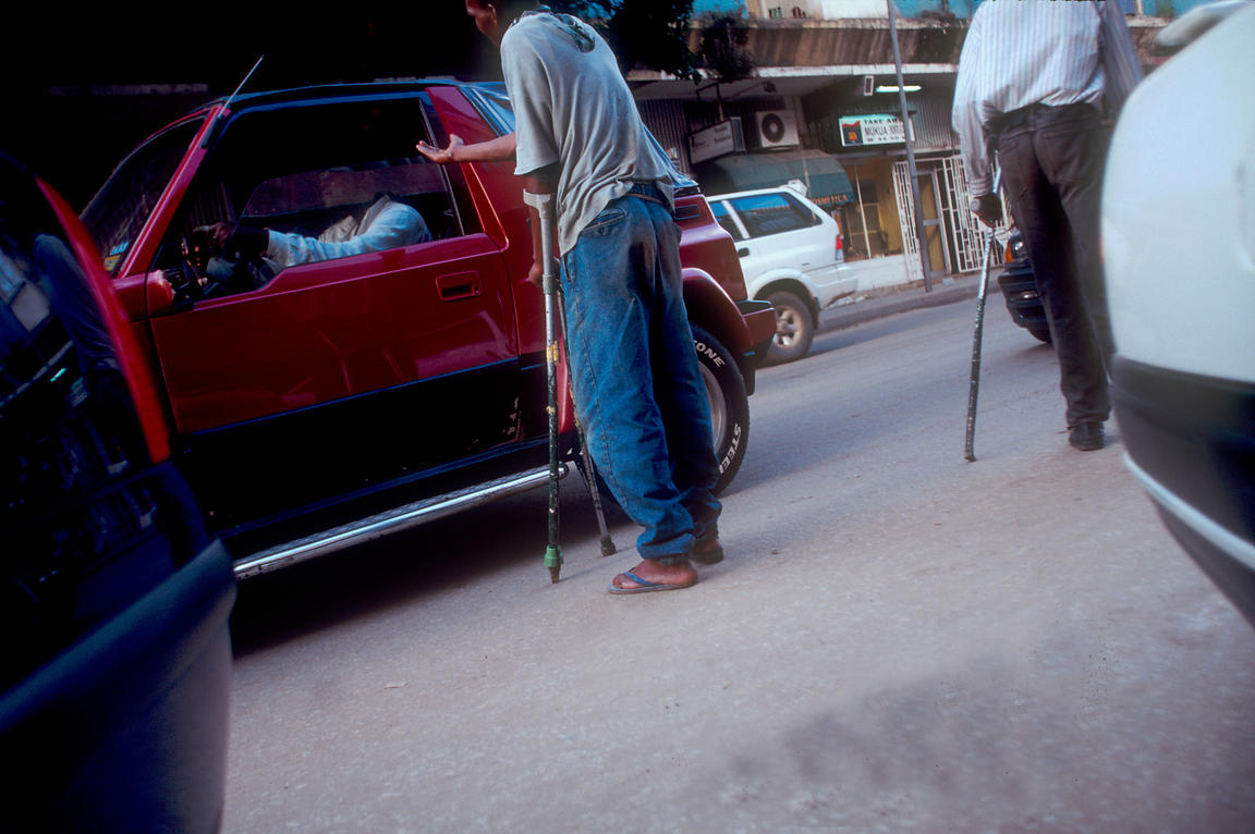Angola - Luanda - Dasilio and his friend, both injured during the Civil War, beg from wealthy Luandans. Angola
