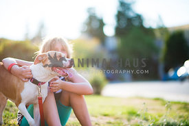 Smiling pitbull mix with young woman