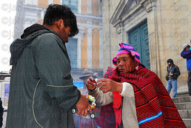 A yatiri or shaman blesses a toy car with alcohol, Alasitas festival, La Paz, Bolivia