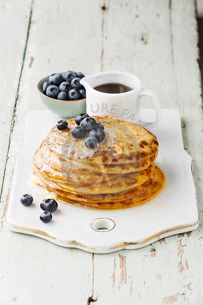 Small pancakes with blueberries, butter and maple syrup