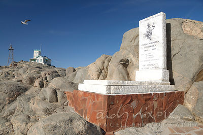 Tombstone and memorial embedded on rocks, a single house and lighthouse tower in the distance, a solitary seagull flying over