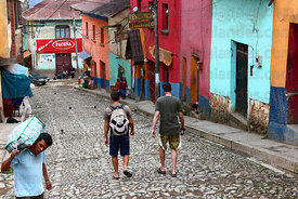 Backpackers walking down colourful colonial street , Coroico , Bolivia