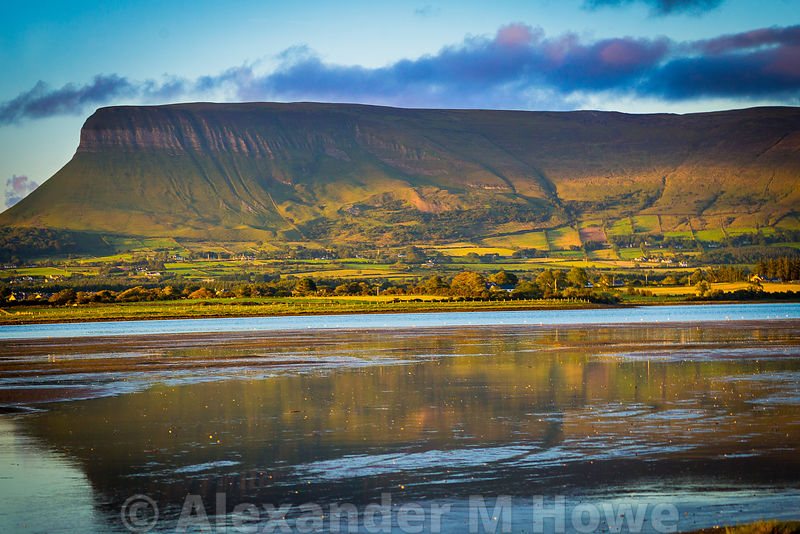 The Benbulbin rock bathed in evening sunlight reflected in the low tide waters of Donegal Bay