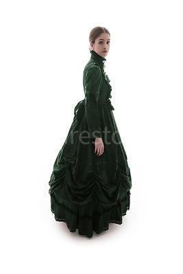 A Victorian woman, in a green dress, looking at camera – shot from eye level.