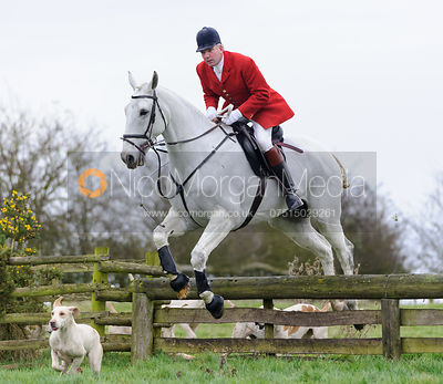 Huntsman Andrew Osborne jumping a hunt jump from the meet