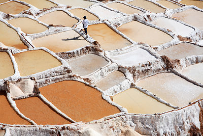Man walking along wall in salt mines, Maras, Peru 2006.