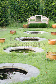 Bench by mini circular ponds and pots. Parkhead, Roseneath, Helensburgh, Dumbartonshire, Scotland, UK