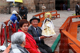 Devotees with Virgen de la Candelaria statue in special seats in front of the cathedral before central mass, Puno, Peru