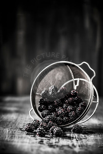 Organic ripe blackberries in an antique colander on a dark wooden surface.
