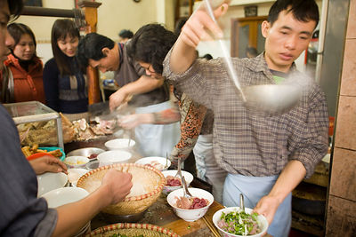 Staff cook and prepare dishes of Pho