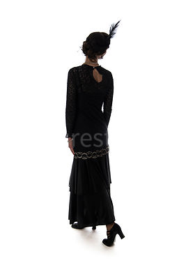 A silhouette of vintage 1920s - 1930s woman in a long black dress with a headband and feather – shot from eye level.