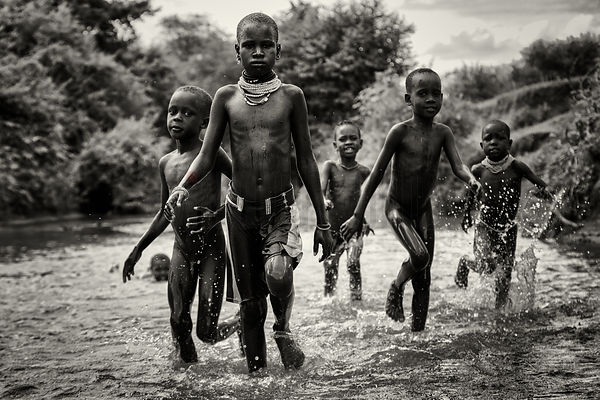 Nyangatom Children Walking in a River